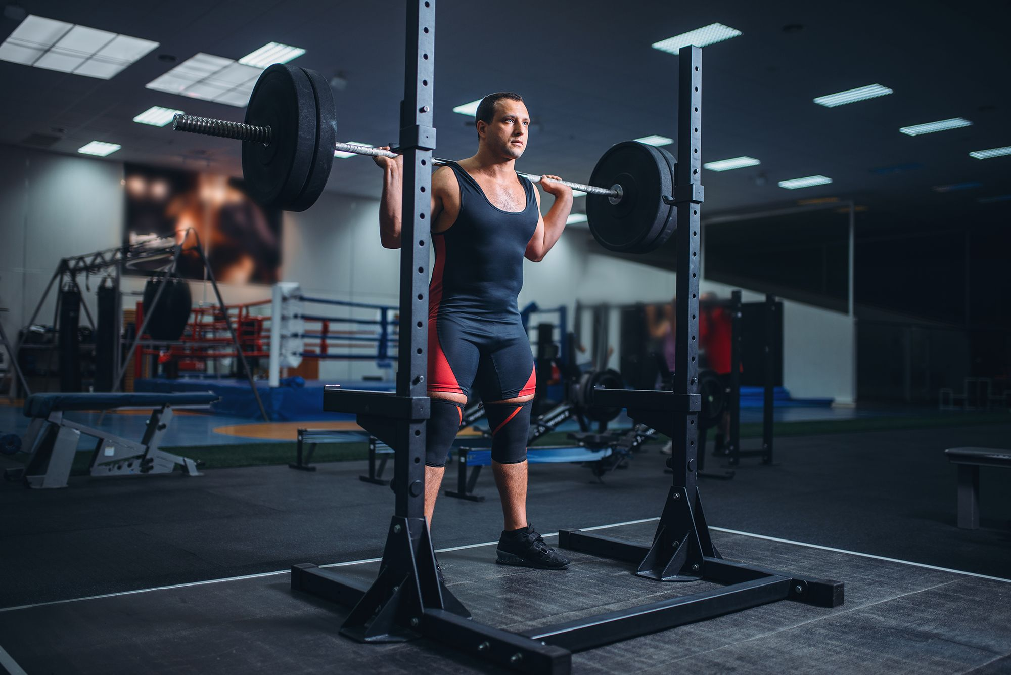 athlete prepares to do squats with barbell