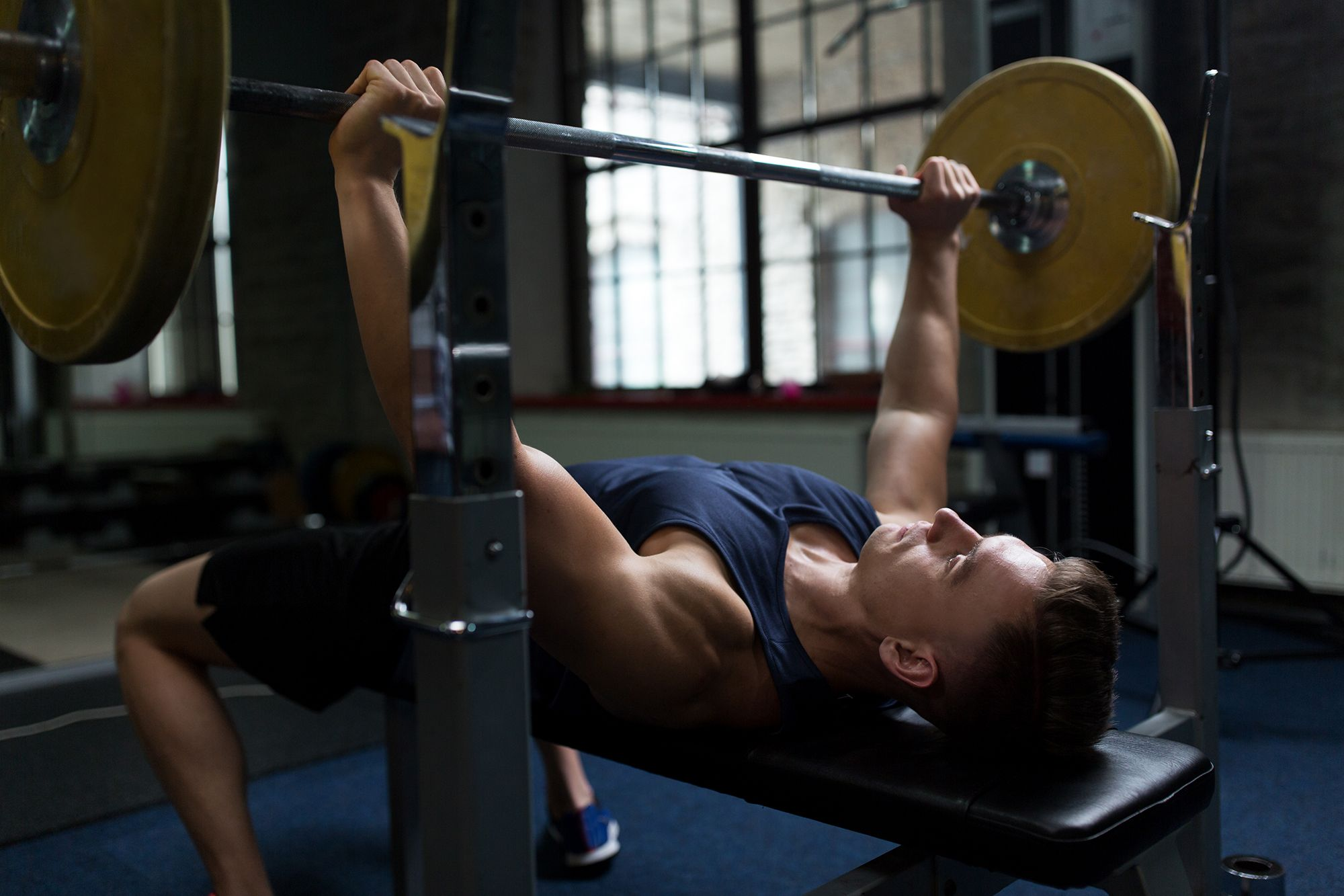 man flexing muscles with barbell in gym