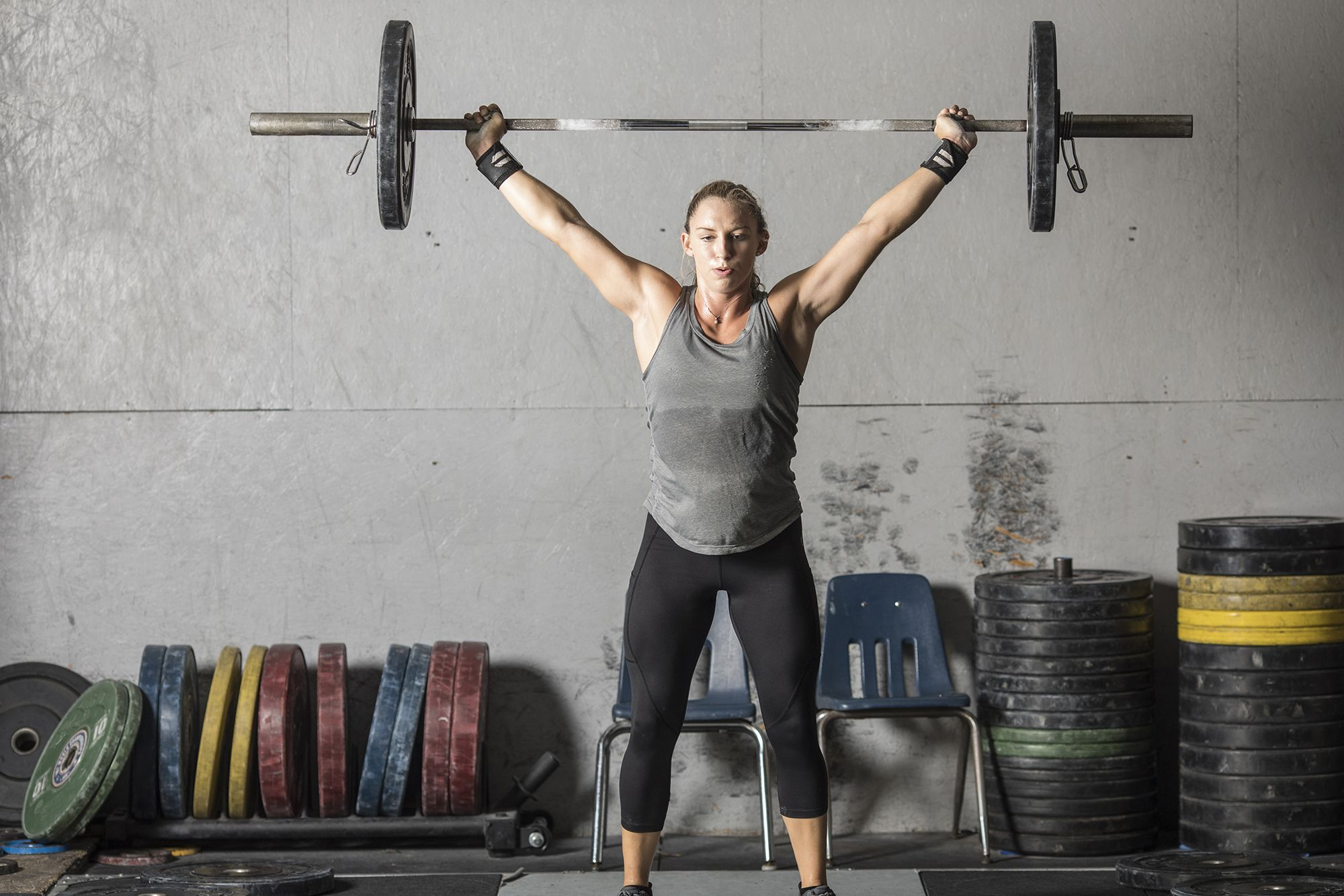 strong woman with heavy barbell over head